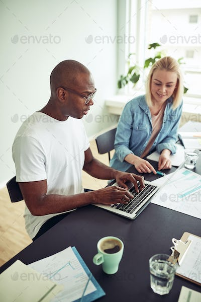 Two businesspeople working with a laptop in an office