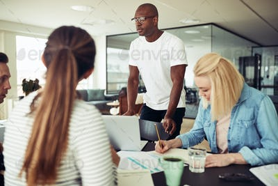 African businessman talking with colleagues around an office table