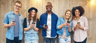 Cheerful multiethnic friends looking at camera standing with phones