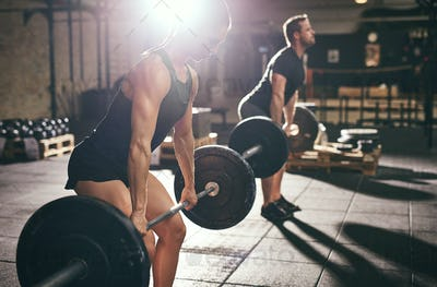 Fit man and woman deadlifting heavy barbells