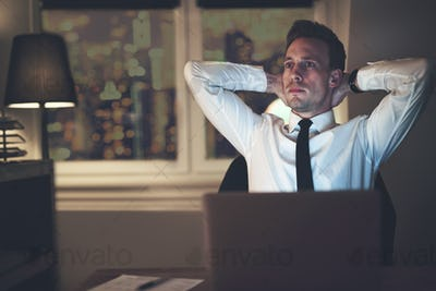 Businessman thinking at office working overtime