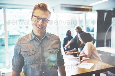Cheerful man in eyeglasses near partners in office