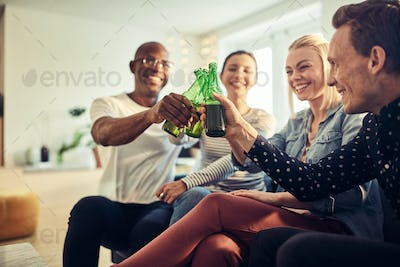 Laughing young businesspeople toasting with beers in an office