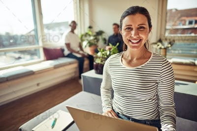 Smiling businesswoman using a laptop with coworkers in the background