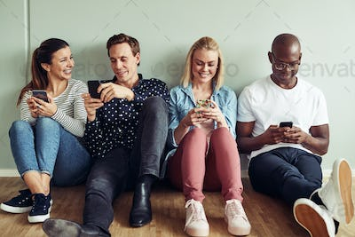 Smiling coworkers sitting on an office floor using their cellphones