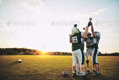 Championship football team raising a trophy together in celebration