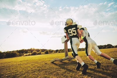 Two American football players doing tackling drills during practice