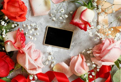 Red roses and small white flowers with a chalkboard
