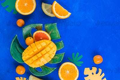 Exotic fruits flat lay. Mango, oranges, kumquat and other tropical fruits on a monstera plate