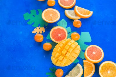 Exotic fruits close-up. Mango, oranges, kumquat and other tropical fruits vibrant blue background