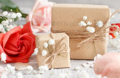 Gift bags and flowers - Red roses and small white flowers on a grey background