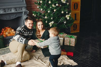 Cute family sitting near Christmas tree