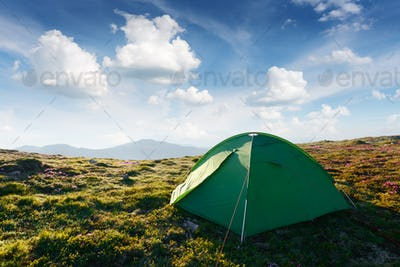 Picturesque scene with green tent and blue sky