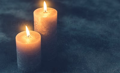 Two burning candles on navy blue background