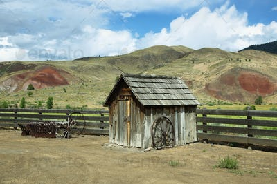 Old wooden shelter and tractor wheels