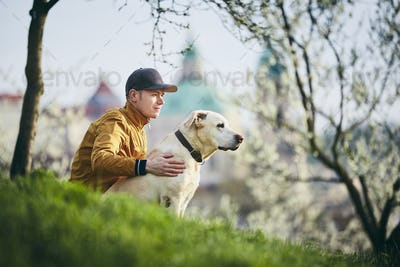 Young man relaxation with dog in public park