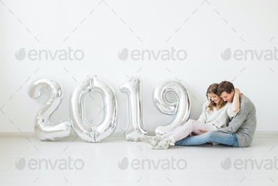 New 2019 Year is coming concept - Romantic young man and woman with silver colored numbers on white