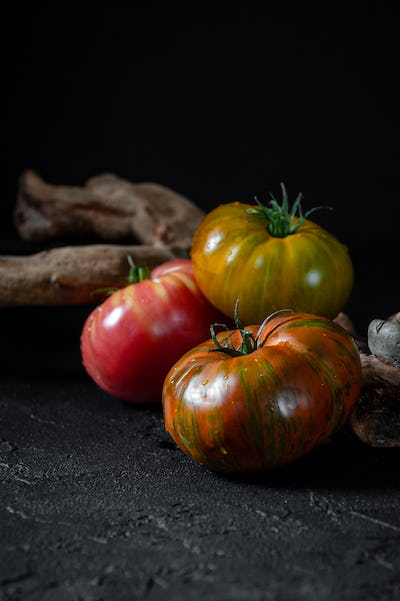 Heirloom tomatoes. Three tomatoes of different colors and a beau