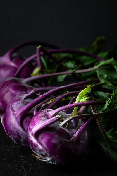 Purple kohlrabi. Shooting on a black background in a low key clo