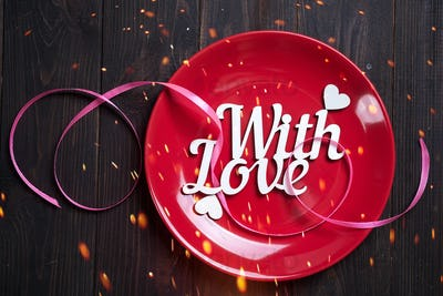 Red plate with wooden letters With love on a wooden background, top view with copy space. Valentine