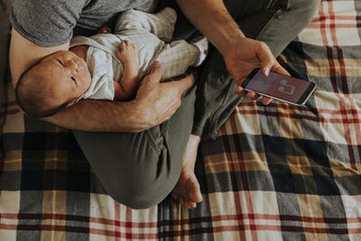 Father holding his baby while using his phone
