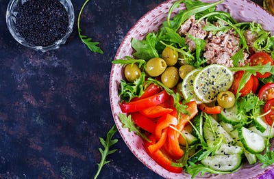 Tuna salad with tomatoes, olives, cucumber, sweet pepper and arugula on rustic background . Top view