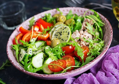 Tuna salad with tomatoes, olives, cucumber, sweet pepper and arugula on rustic background