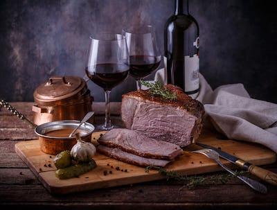 Roast beef and red wine, dark photo