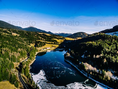 Aerial view of frozen river with dam. Beautiful winter landscape in Italy