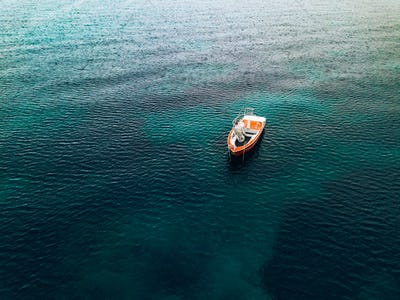 Aerial view of small fishing boat at sea, Greece.