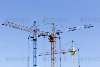 Industrial landscape with silhouettes of cranes on the sky backg