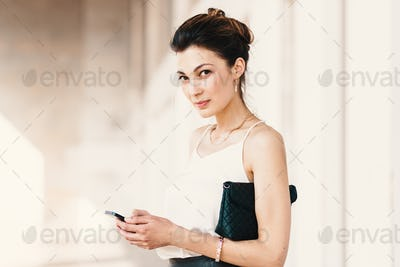 Portrait of a smiling elegant young woman using a smart phone