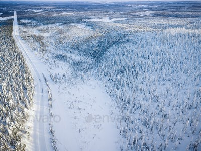 Aerial view of snow covered winter forest and road. Beautiful rural landscape in Finland