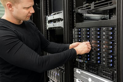 Male Technician Adjusting Hard Drives In SAN At Datacenter