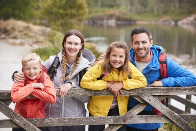 Young family leaning on a wooden fence in the countryside, looking at camera, close up