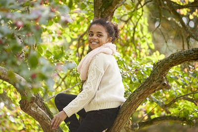 Young girl sitting in an Autumn tree, turning and smiling to camera, side view