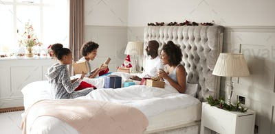 Young mixed race family sitting on bed opening gifts in parentsÕ bedroom on Christmas morning