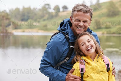 Caucasian pre-teen girl standing with her father on the shore of a lake
