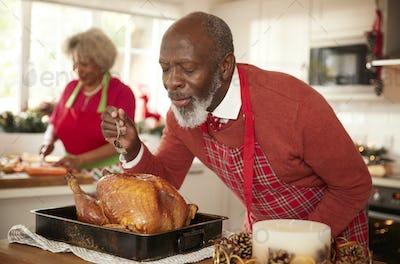 Senior black man basting roast turkey in preparation for Christmas dinner