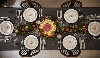 Christmas table setting with baubles arranged on plates, overhead view