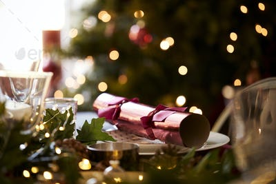 Close up of Christmas table setting with a Christmas cracker arranged on a plate