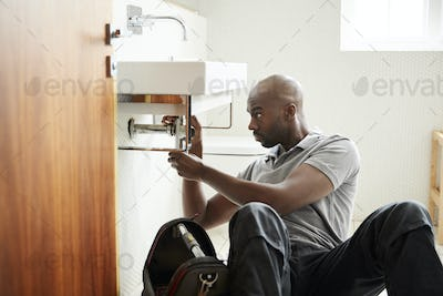 Young black male plumber sitting on the floor fixing a bathroom sink, seen from doorway