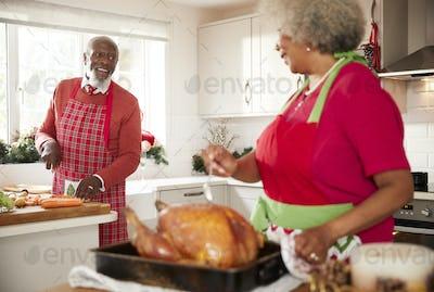 Senior black woman preparing a roast turkey for Christmas dinner turns to talk to her husband