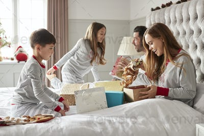 Parents Opening Gifts From Children As They Sit On Bed Exchanging Present On Christmas Day