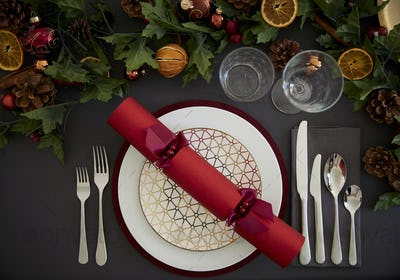 Christmas table setting with a red Christmas cracker arranged on a plate