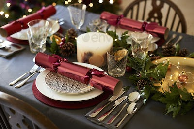 Close up of Christmas table setting with Christmas crackers arranged on plates