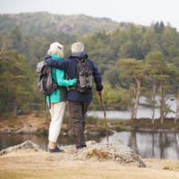 Senior couple standing embracing and admiring the view of a lake, back view