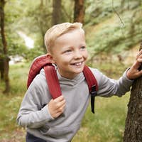 Pre-teen boy taking a break leaning on a tree during a hike in a forest, elevated view, close up