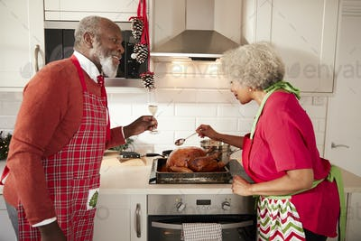 Mature black couple preparing Christmas dinner in their kitchen, smiling