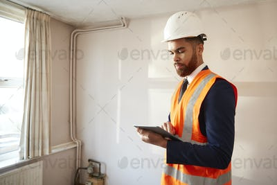 Surveyor In Hard Hat And High Visibility Jacket With Digital Tablet Carrying Out House Inspection